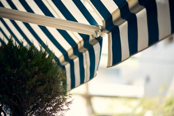 A Low Angle View Of A Blue And White Retractable Awning On A Greek Patio
